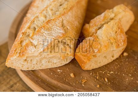 Close up cut fresh french baguette on wooden cutting board