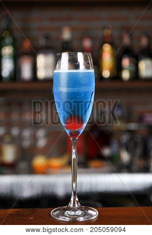 Blue cocktail soda and cherry in bar