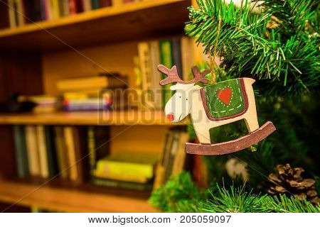 Close up of small wooden deer hanging on Christmas tree