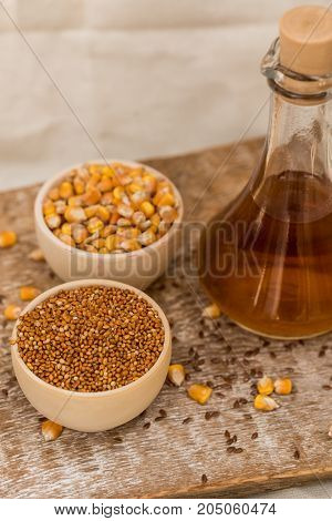Close up two wooden bowls with corn and millet grains and decanter with seed oil organic food concept