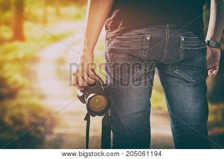 Man is holding a camera against a landscape background.