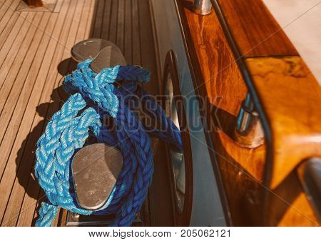 blue rope wrapped around a bollard on the deck of the yacht.