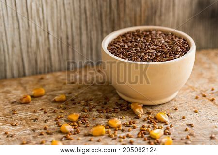 Close up wooden bowl filled with flax seed and different seeds scattered on table
