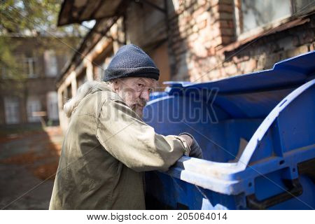 Homeless old man in search for food. Poor tramp hungry, rummaging for some food in garbage.