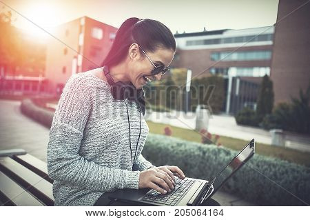 Woman laughing while typing on laptop outdoors in sunset