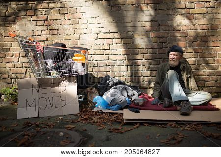 Homeles man sitting on ground in the strteet. Tramp sitting on card board by the brick wall.
