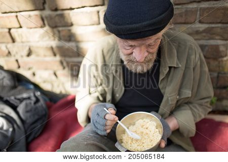 Portrait of homeless old man holding bowl with porridge. Tramp living in the streets of the city, sitting by the wall, eating.