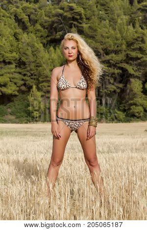 Fit model in a leopard print bikini posing in field.