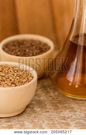 Close up wooden bowl with wheat grains and seed oil in decanter organic food concept