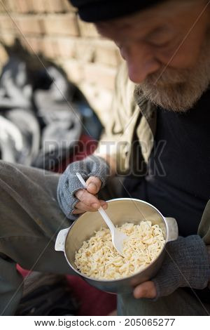 Close up view of an old tramp, eating. Homeless man having lunch in the street.