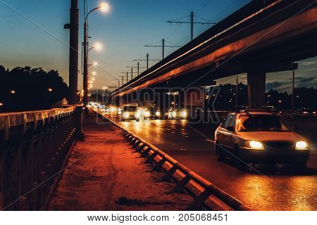 Night road, big bridge and a lot of cars, evening traffic, city lights, dark toned