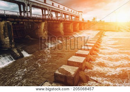 Hydro power plant or hydroelectric power station at sunset, toned