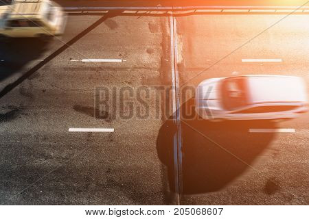 Motion blur of cars in sunlight, aerial view or top view over asphalt road, blurred cars, transportation concept