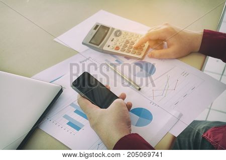 young man hand using smart phone and calculate finance cost with calculator business strategy diagram report and laptop computer on desk at home office income and expenses economy concept