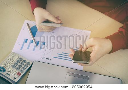 top view of hand entering security code with smart phone and paying with credit card business strategy diagram report on desk at home office income and expenses payment and shopping online concept
