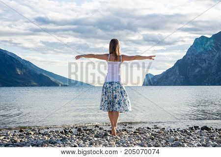 Woman meditating at the lake Garda. Italy