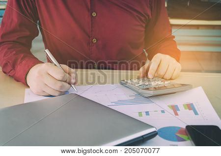 young man working calculate finance cost with calculator and writing with business strategy diagram report laptop computer smart phone on desk at home office income and expenses economy concept
