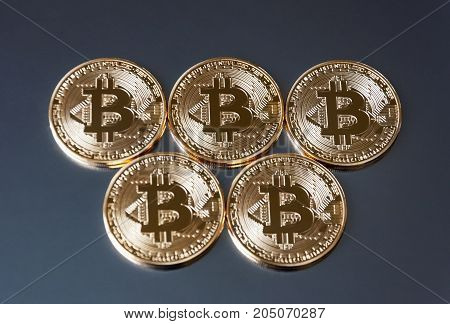 A few gold coins bitcoin lie on a dark background. The concept crypto currency