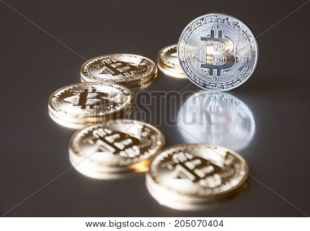 A few gold and silver coins bitcoin lie or stay on edge on a dark background. The concept of crypto currency