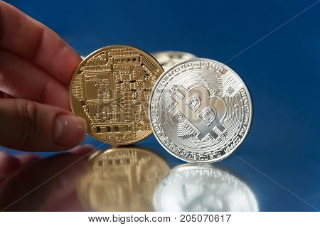 Hand holds a gold coin bitcoin on a blue background. Nearby is a silver coin bitcoin on the edge. The concept of crypto currencies.