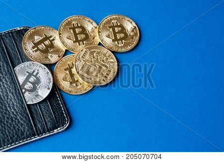 Black leather wallet on a blue background with several gold and silver coins of bitcoins falling out of their pockets. The concept of crypto currencies.