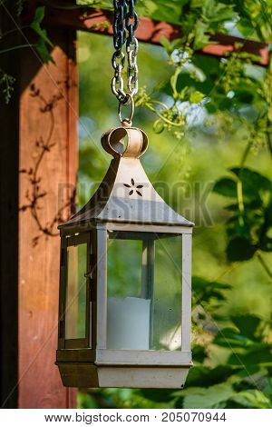Ancient lamp with candle as a decorative accessory of a garden