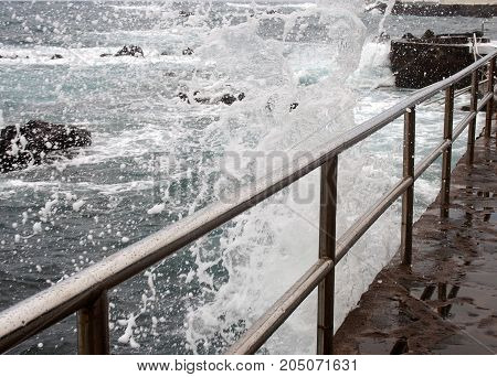 High dramatic waves breaking over a seafront promenade with white surf steel railings and blue sea