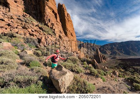 Trail running girl in mountains on rocky path. Cross country runner training with backpack in inspiring nature dirt footpath on Tenerife Canary Islands Spain.