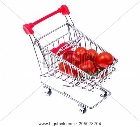 Ripe red cherry tomatoes in small cart. Studio Photo