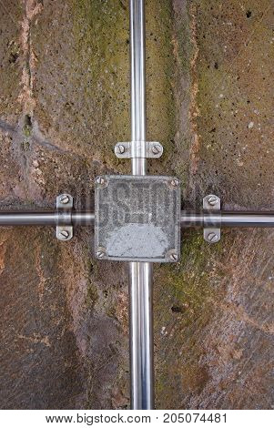 outdoor electrical junction box in metal with conduits and fixtures fastened to a stone wall