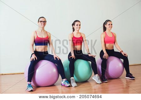 Group of smiling women doing exercises on fitness ball in the gym.