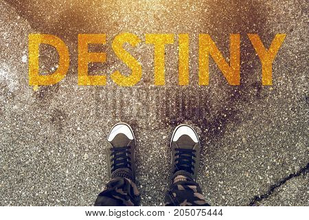 Young person standing on the road with Destiny imprint on pedestrian walkway. Making right choices and deciding about future steps determines your fate.