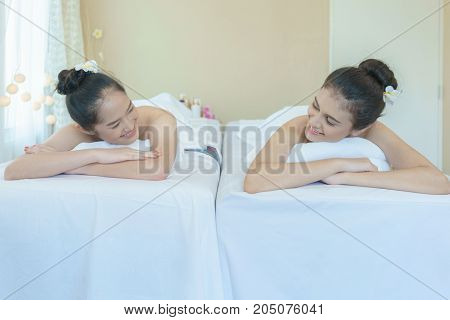 Beautiful Asian young woman smiling at each other while lying on massage table waiting for spa treatment