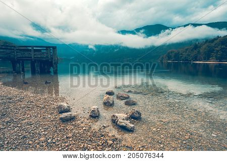 Wooden pier on the lake. Dramatic moody image with rainy clouds above the water surface. Image is taken on lake Bohinj in Slovenia.