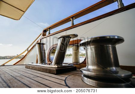 luxury yacht steel bollard. steel bollard and the warping drum on the wooden deck of the boat. Luxury vacation on the water.