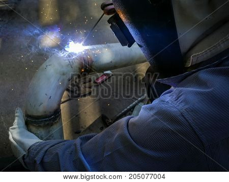 Worker man in personal protective equipment welding pipe by transformer welding machine.