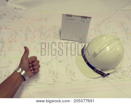 Filter color effect of Defocus background industrial blueprint on table with safety helmet calendar and left hand.