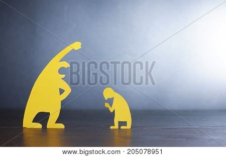 Big screaming man against small miserable man made from yellow paper