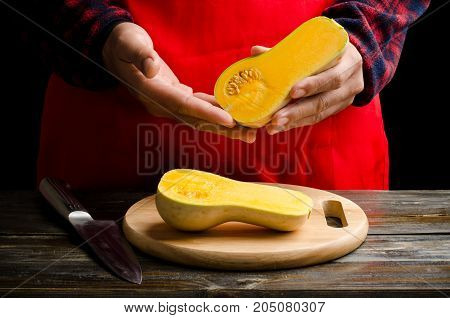 Hand holding butternut squash and cutting for cooking