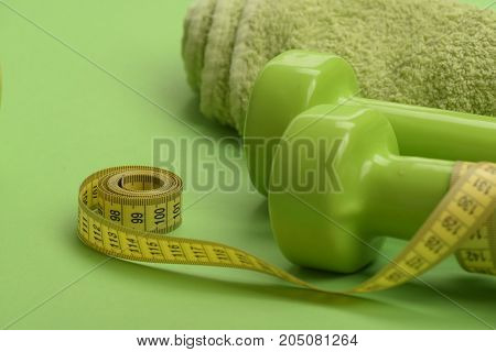 Tape Measure In Yellow Color Near Barbells, Close Up