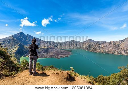 Woman enjoy and happy with active volcano Baru Jari Lake Segara Anak and summit of Rinjani mountain view after finished climbing at Rinjani mountain Lombok Indonesia.