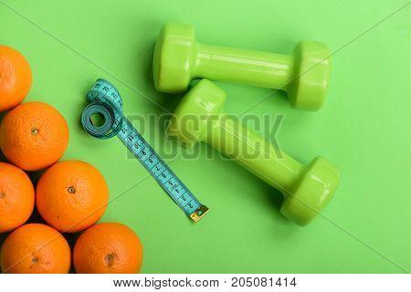 Oranges Near Dumbbells, Cyan Measuring Tape On Green Background,