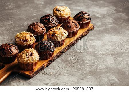 Different homemade muffins with chocolate and berries, selective focus. Copy space.