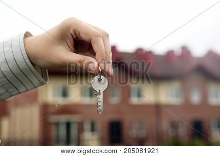A man's hand holds the keys on the background of new buildings