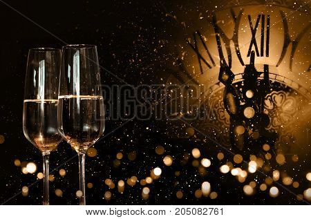 New year congratulations with champagne and a clock in dark background with snowflakes and golden bokeh