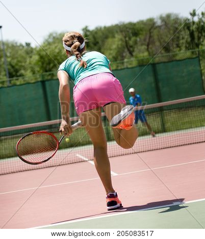 girl with a racket playing tennis on the court .
