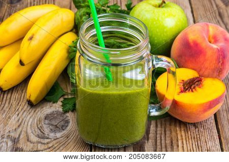Freshly blended green  smoothie in glass jar on wooden background. Studio Photo
