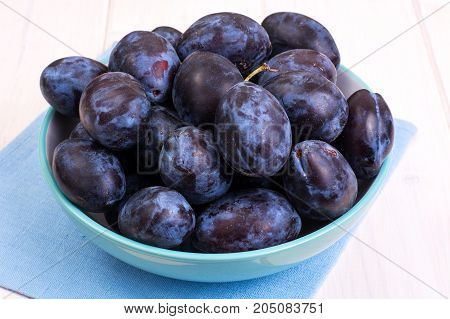 Blue ceramic bowl with plums on white wooden background. Studio Photo