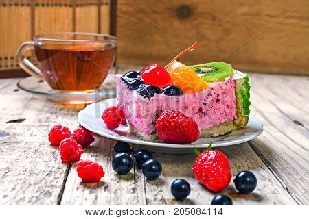 Sweet cake with berries and fruits. Cake with orange strawberry raspberry and currant. View from above.