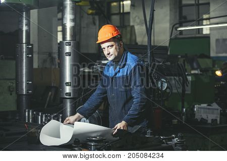 Working In Production Against A Background Of Machines From The Engineering Drawings In His Hands Wh